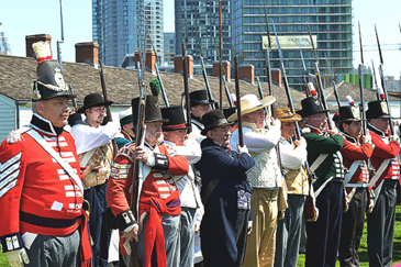 Re-enactors in regular uniforms and a militia dressed more casually present arms at Battle of York Day ceremonies at Fort York on 27 April 2013. Photo: Department of National Defence